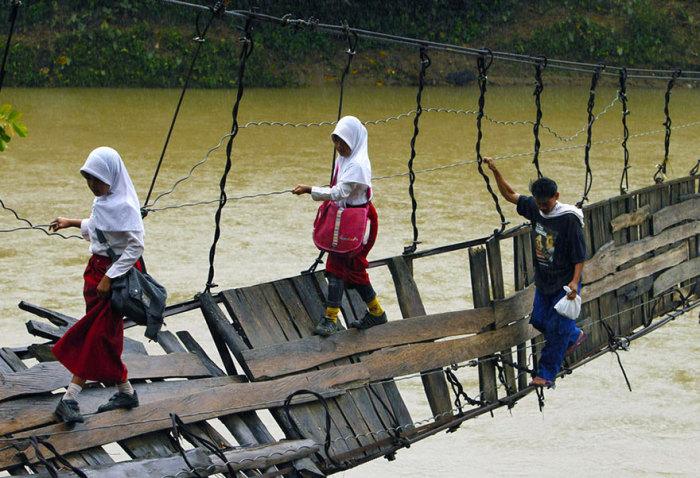 Индонезийские дети добираются в школу по опасному мосту через реку.