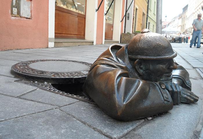 Скульптура мужчины, вылезающего из канализации.
