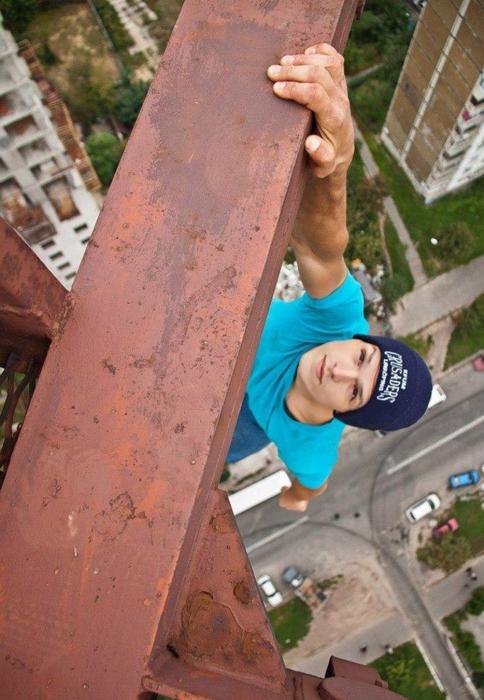 Нужно быть настоящим смельчаком, чтобы повиснуть, одной рукой зацепившись за балку на крыше многоэтажки.