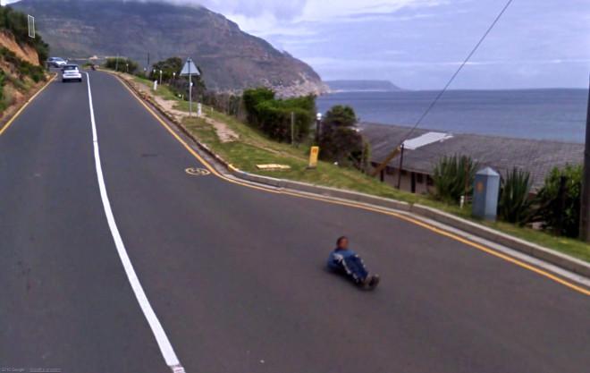 Подросток едет по проезжей части лежа на скейте.