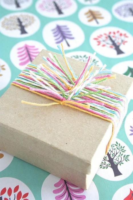 С помощью небольших отрезков разноцветных нитей можно создать необычный вариант дизайна подарка.