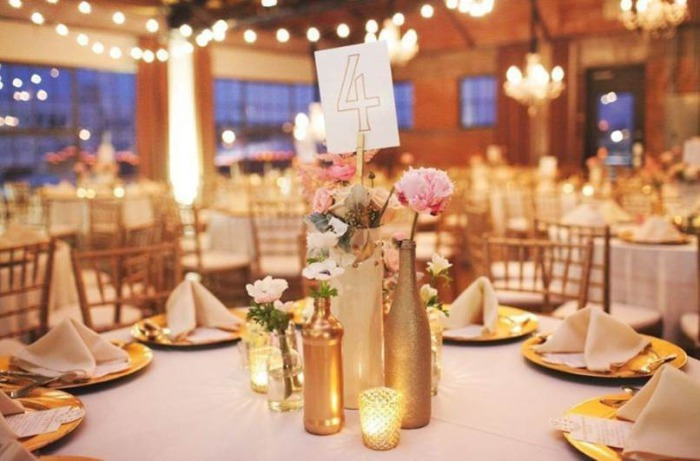 Несколько бутылок в золотом цвете и свечки будут потрясающе смотреться на свадебном столе.