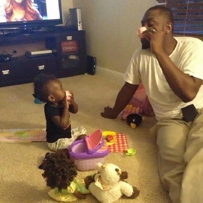 Папа, который пьет воображаемый чай со своей маленькой дочкой.