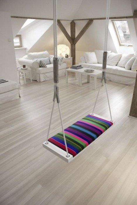 Качели из обычного каната и красивого разноцветного сиденья могут полностью преобразить чердак в доме.