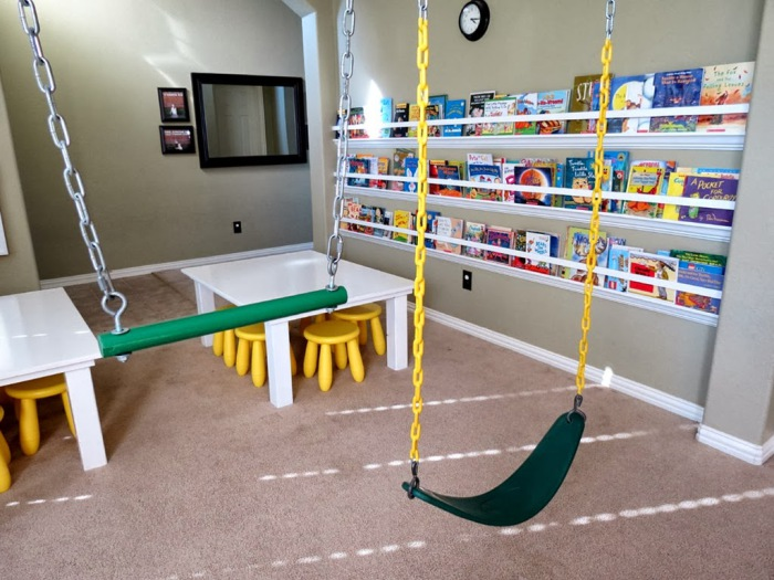 Качели в детской комнате для двоих детей. Не стоит заставлять одного из детей ждать своей очереди поиграть