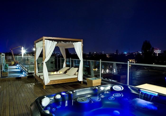 Элегантная кровать возле джакузи на крыше дома.