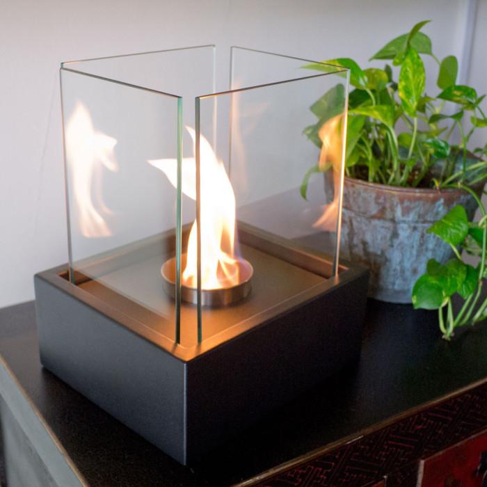 Элегантная лампада, имеющая прочное квадратное основание и четыре стеклянные стенки.