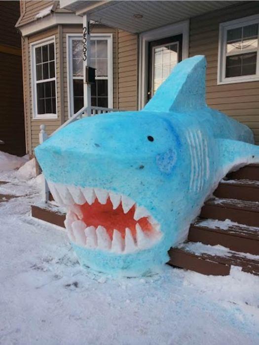 Огромная снежная акула на крыльце дома.