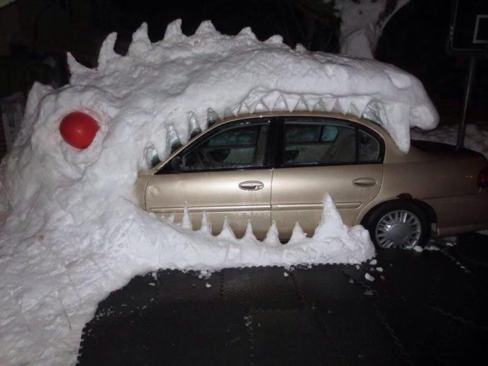 Снежная годзилла, пожирающая автомобиль.