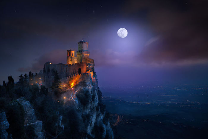 Замок на утесе на фоне ночного неба.