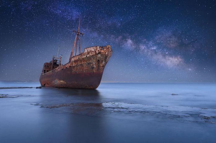 Брошенный корабль под великолепным ночным небом.