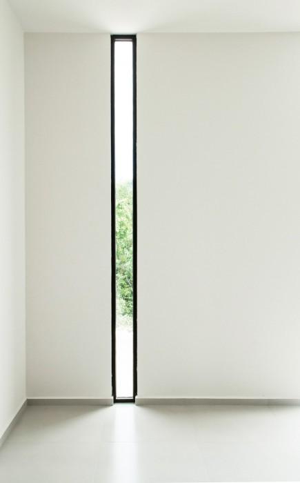 Длинное и узкое окно создаст особую атмосферу в комнате, так как оно способно пропускать совсем немного света.