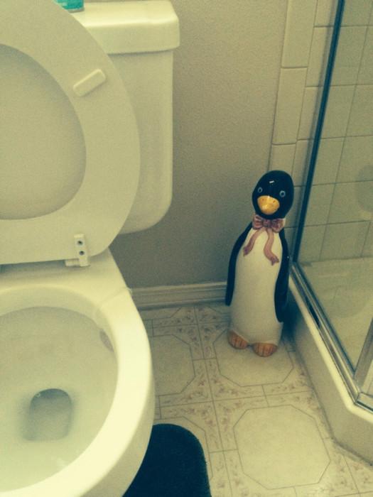Статуя пингвина, стоящая в туалетной комнате.
