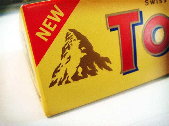 Медведь на фоне горы на логотипе шоколадного батончика.