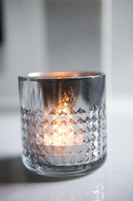 Оригинальный подсвечник серебристого цвета из стеклянного стакана.