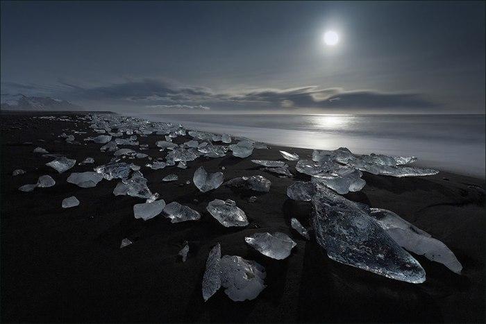 На фоне черного песка красиво выделяются огромные глыбы белого льда.