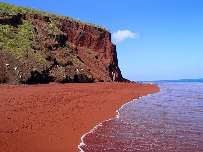 Красный песок на пляже на Галапагоссе.