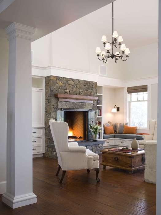 Прекрасная гостиная с камином и угловым диваном на подоконнике.