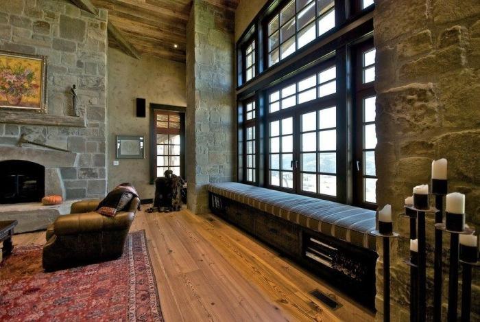 Мягкая скамейка у окна большой гостиной в рустикальном стиле.