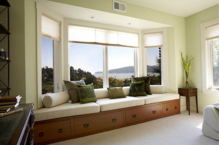 Элегантный белый диван на подоконнике с подушками насыщенного зеленого цвета.