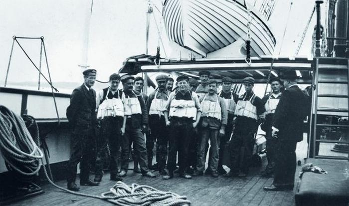 Команда Титаника позирует в спасательных жилетах.