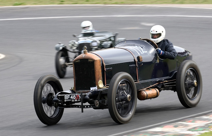 Пример открытого гоночного авто начала XX века. Шлемы гонщиков современные.