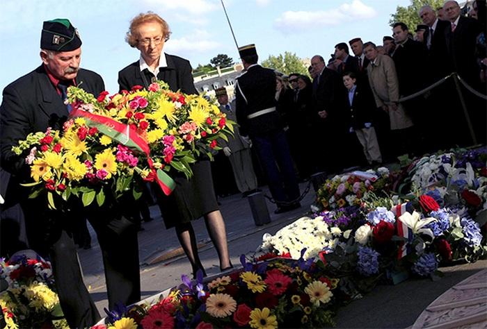 Ветеран Второй мировой войны возлагает цветы к Триумфальной арке в Париже.