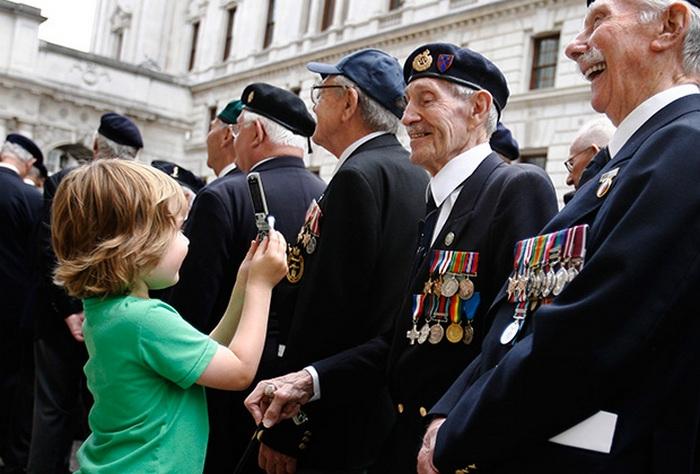 В Лондоне мальчик фотографирует ветеранов у кенотафа на улице Уайтхолл/