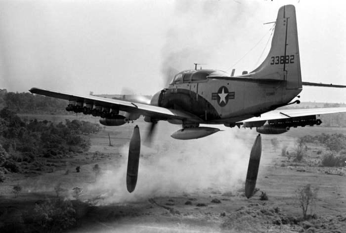 Американский штурмовик Douglas A-1 Skyraider сбрасывает бомбы напалмовые бомбы на позиции войск Северного Вьетнама.