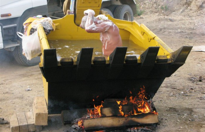 Принимают ванну в ковше экскаватора.