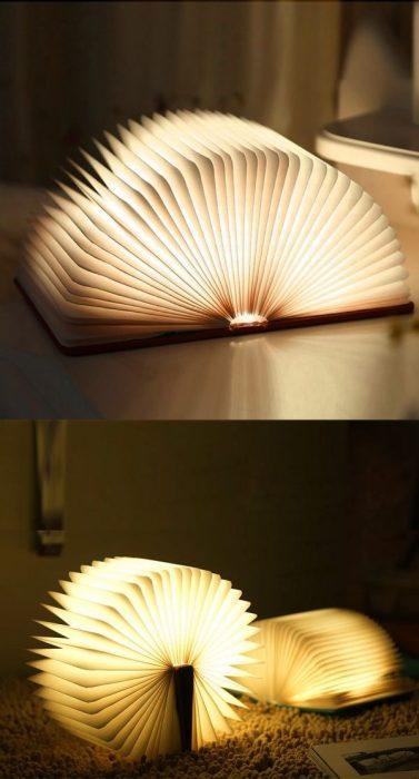 Прикроватный светильник в форме книги с открытыми станицами, которые светятся.