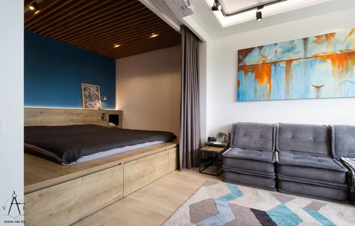 Деревянная ниша со шторой отделяет зону спальни от гостиной в апартаментах площадью 48 квадратных метров.