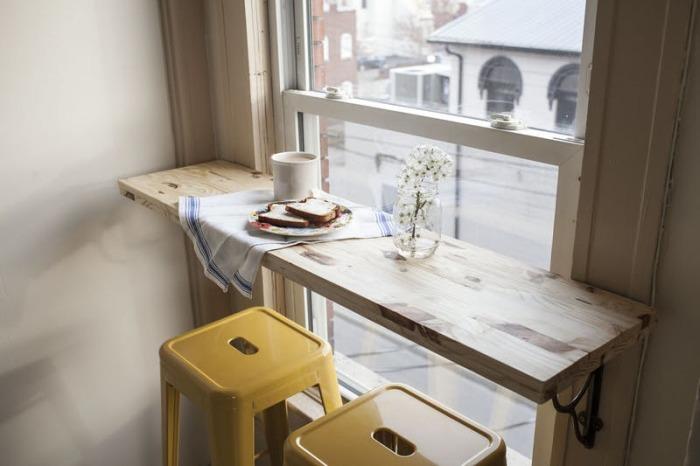 Можно заменить обычный подоконник деревянной полкой и сделать из нее небольшой столик.