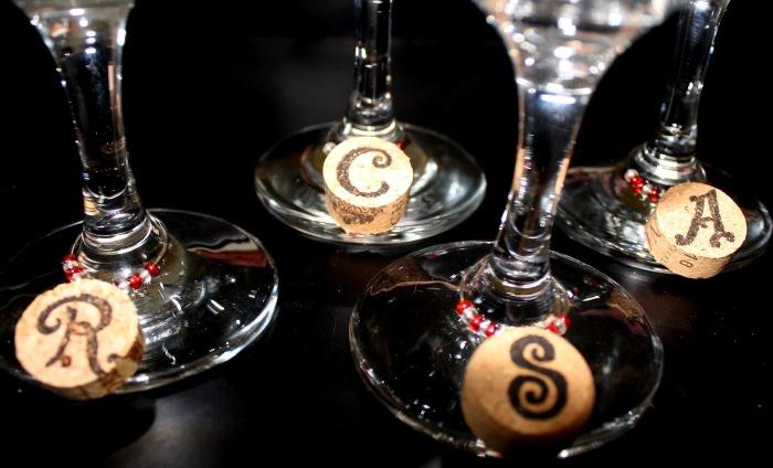 Из винных пробок можно сделать маленькие бирочки, которые украсят бокалы и помогут гостям не перепутать стаканы.