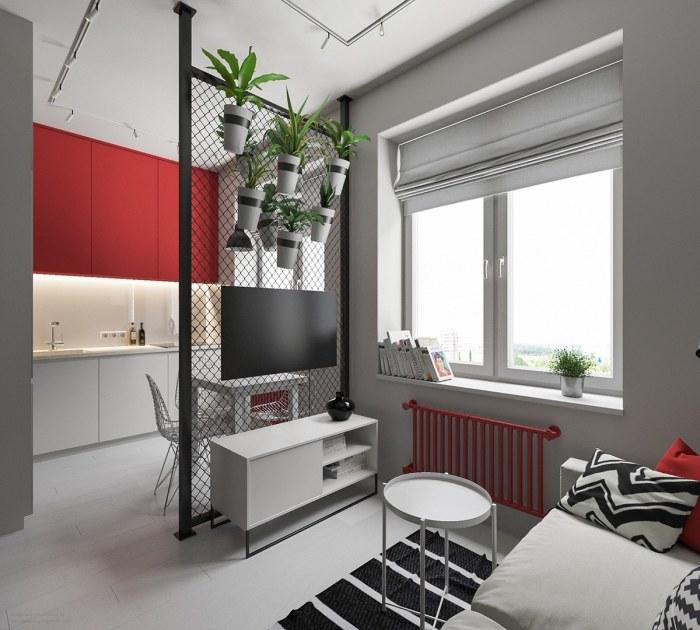 Сетчатая перегородка с живыми цветами делит пространство комнаты на гостиную и кухню.