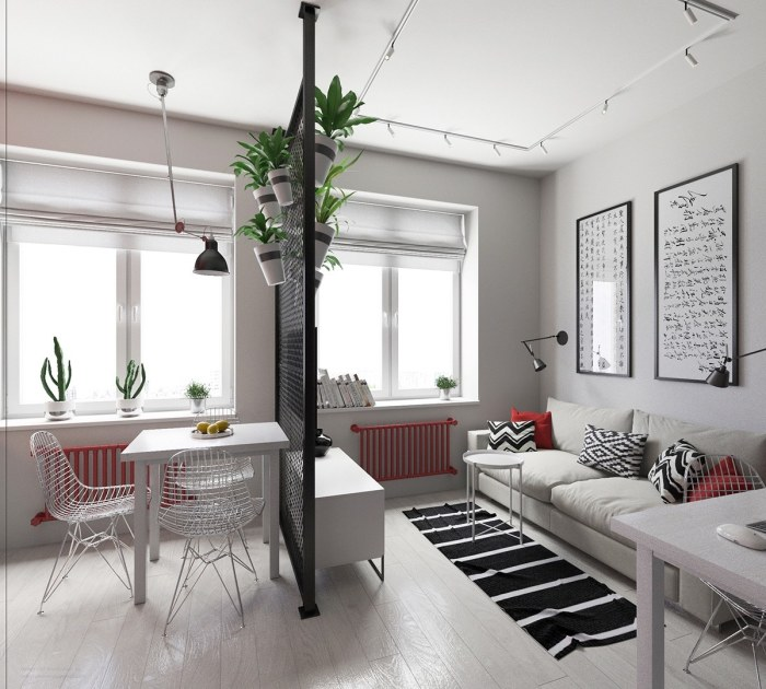 Обеденная зона и гостиная, разделенные черной сетчатой перегородкой.