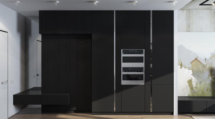 Огромный черный гарнитур с матовой поверхностью, в который встроена кухонная бытовая техника.