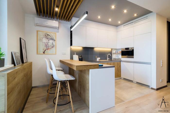Кухонный гарнитур и обеденная зона в белом цвете с деревянными акцентами.