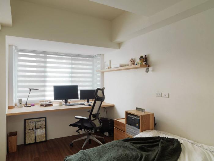 Рабочая зона, расположенная в спальне возле окна.