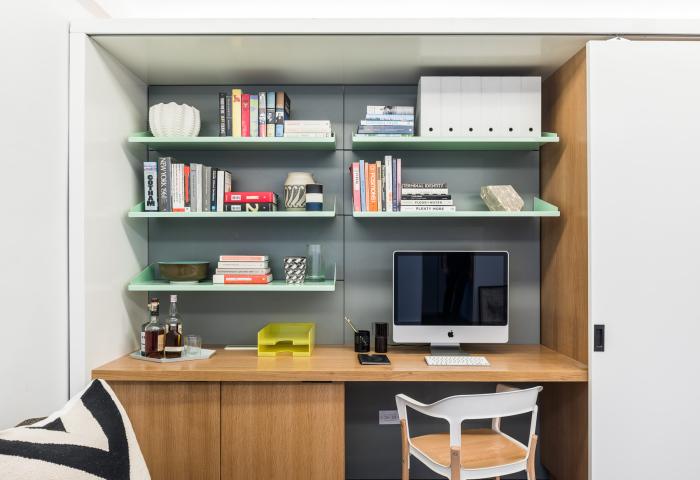 Рабочий стол в гостиной, который можно спрятать за раздвижными дверями.