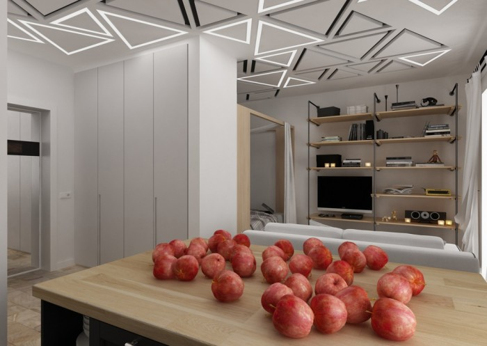 Белый диван разделяет пространство между гостиной и кухней.