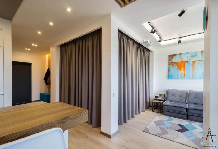 Ниша с двуспальной кроватью, гостиная комната и обеденная зона находятся в пределах одного открытого пространства.