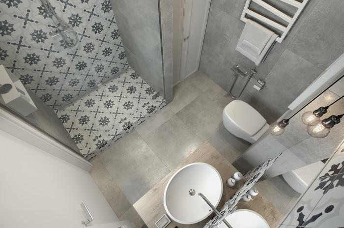 Ванная комната с красивой плиткой в спокойных серых тонах.