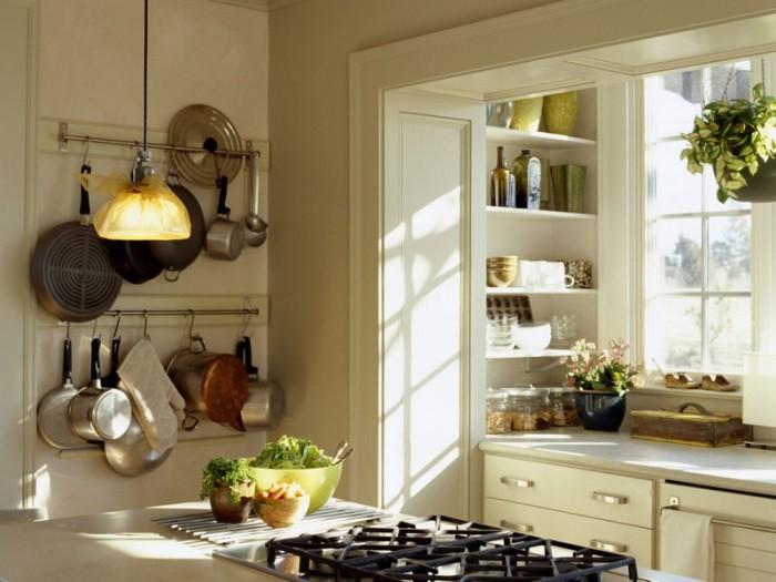 Громоздкие кастрюли и сковородки, а также другие предметы кухонного обихода можно не только складывать в шкафчики, но и вешать прямо на стенах.