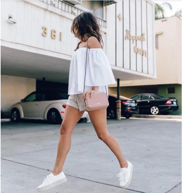 Блуза с открытыми плечами в сочетании с бежевыми шортами и кроссовками - наряд, который помогает визуально сделать ноги более длинными.