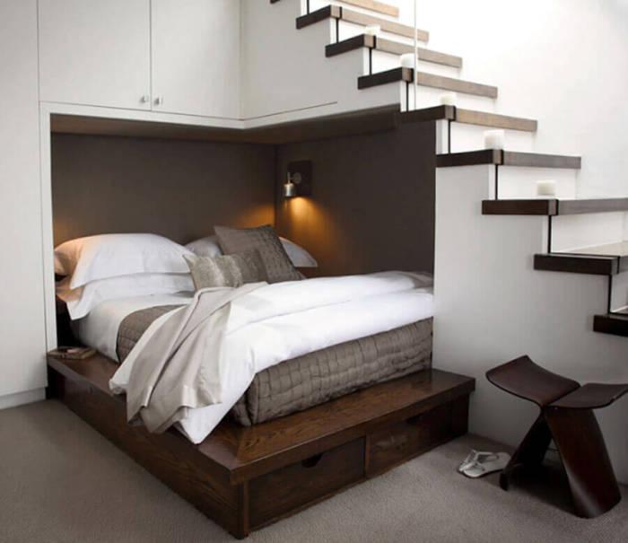 Для экономии пространства можно обустроить спальное место прямо под лестницей.