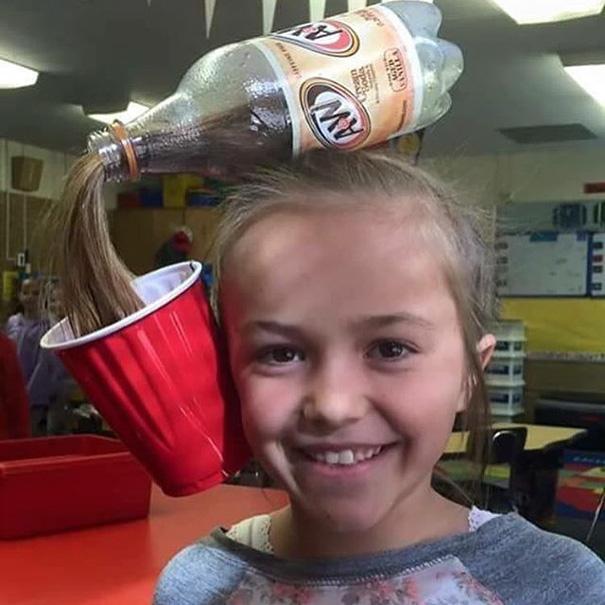 Интересную прическу, имитирующую разливающийся напиток, можно сделать из пластмассовой бутылки и одноразового стаканчика.