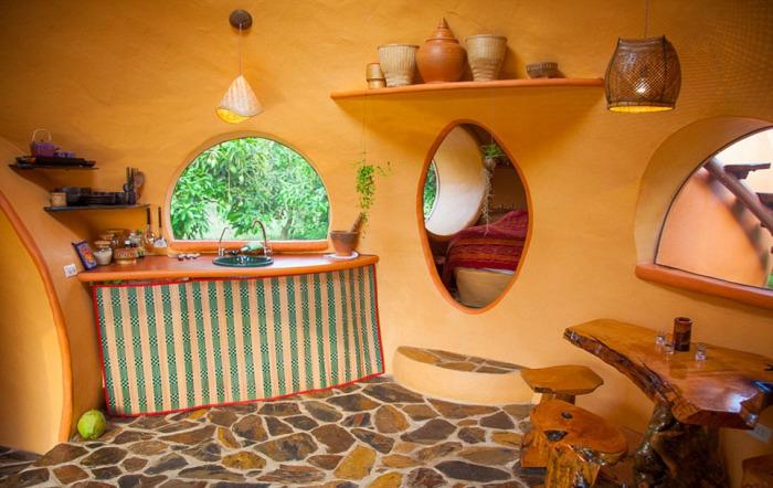 Кухня в маленьком доме, который построен посреди манговой рощи.