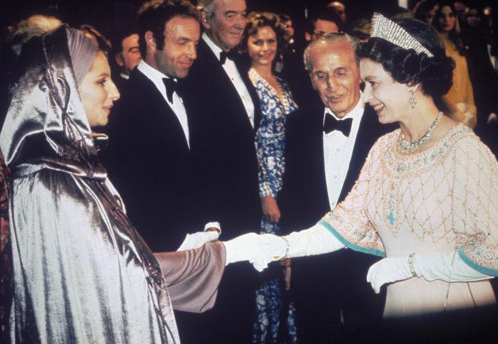 Известная американская певица, актриса, режиссёр и продюсер Барбара Стрейзанд на встрече с королевой Елизаветой Второй в 1975 году.