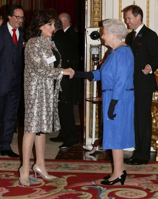 Знаменитая британская актриса, продюсер и писательница Джоан Коллинз на встрече с королевой Великобритании в 2014 году.